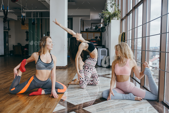 Young attractive women practicing yoga near window - Stock Photo - Images