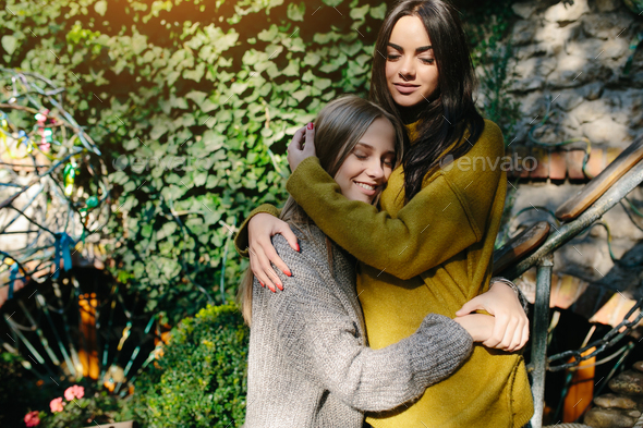 Two girls hugging in the shade of of leaves - Stock Photo - Images