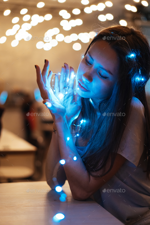 Woman holding glowing christmas garland in hands - Stock Photo - Images