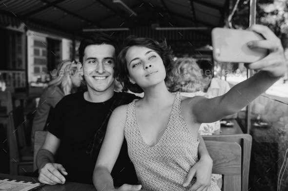 guy and the girl make selfie in the cafe outside - Stock Photo - Images