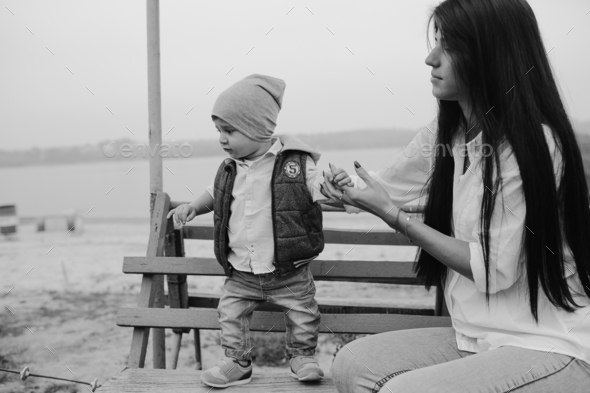 Mother and young son together on a bench - Stock Photo - Images