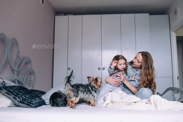Mother, father,and baby on the bed - Stock Photo - Images