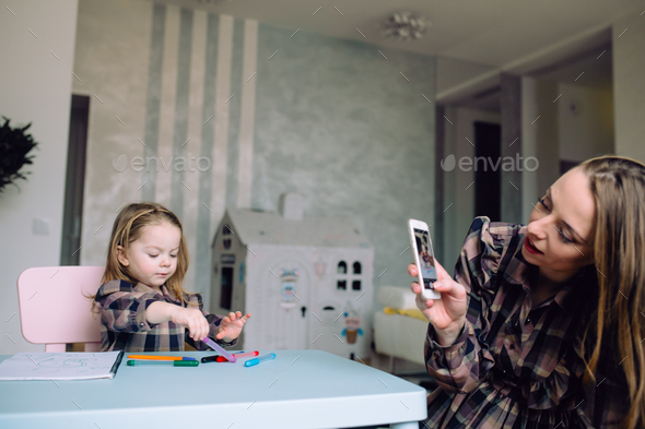 Happy little girl drawing at home with mom - Stock Photo - Images