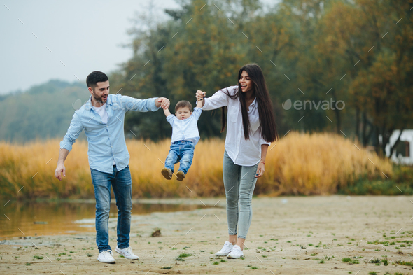 Young family walking at the beach - Stock Photo - Images
