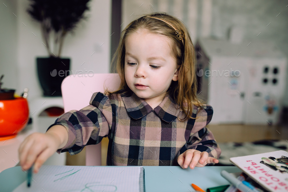 Happy little girl drawing at home - Stock Photo - Images
