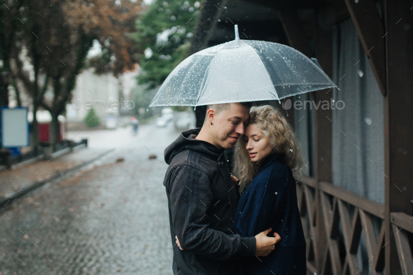 Couple on the street with umbrella - Stock Photo - Images