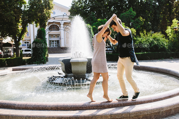 beautiful young couple at the fountain - Stock Photo - Images