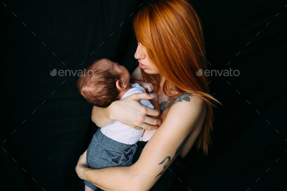 Young mother woman holding her child baby - Stock Photo - Images