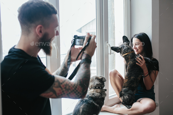 man photographs the girl at the window - Stock Photo - Images