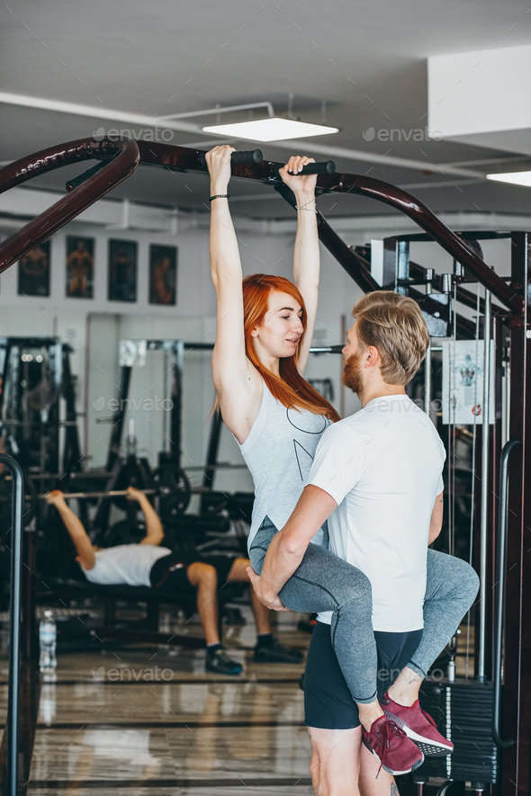 guy hepl girlfriend on training in gym - Stock Photo - Images