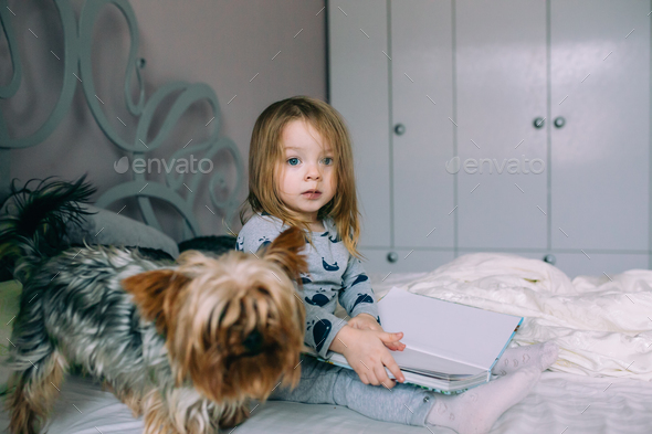 Little girl sitting in bed - Stock Photo - Images