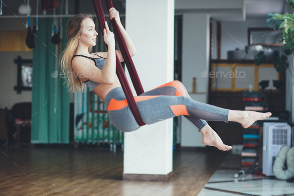 Young woman performing antigravity yoga exercise - Stock Photo - Images