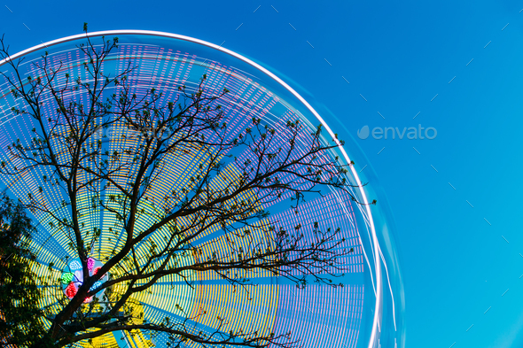 Tree Branches Against Backdrop Of Bright Spinning Ferris Wheel A - Stock Photo - Images