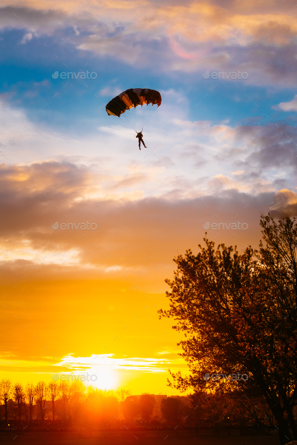 Skydiver On Colorful Parachute In Sunny Sky - Stock Photo - Images