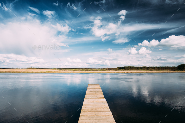 Old Wooden Boards Pier On Calm Water Of Lake Or River At Evening