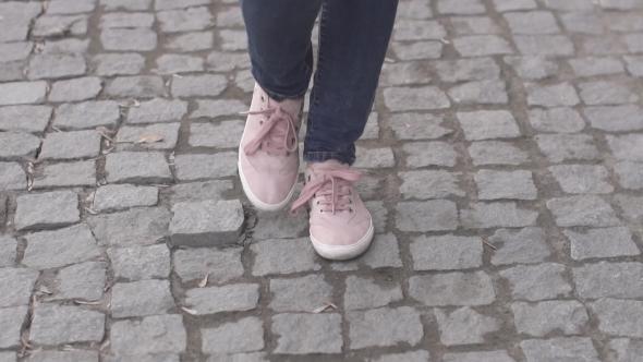 Girls Feet in Sneakers Walking on the Sidewalk