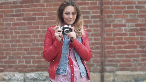 Portrait of a Young Charming Woman with a Film Retro Photo Camera in Hands