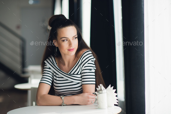 Portrait of an adult beautiful woman looking through window while sitting at a table in a cafe. - Stock Photo - Images