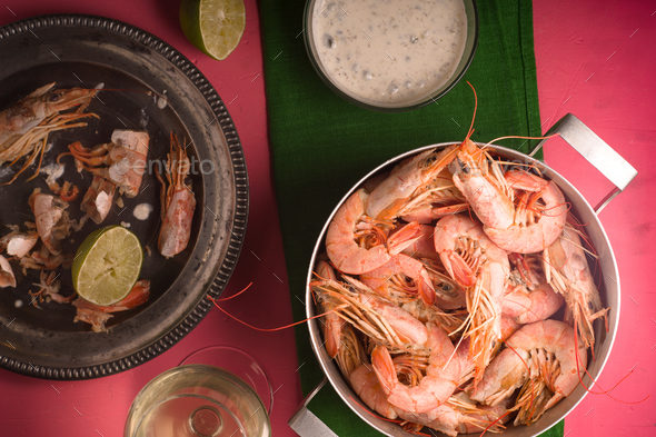 Shrimp on a pink table, glass with white wine and sauce - Stock Photo - Images