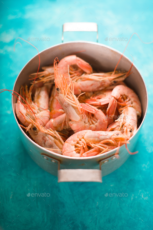 Casserole with shrimps on a turquoise table - Stock Photo - Images
