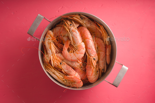 Casserole with shrimp on a bright pink table - Stock Photo - Images