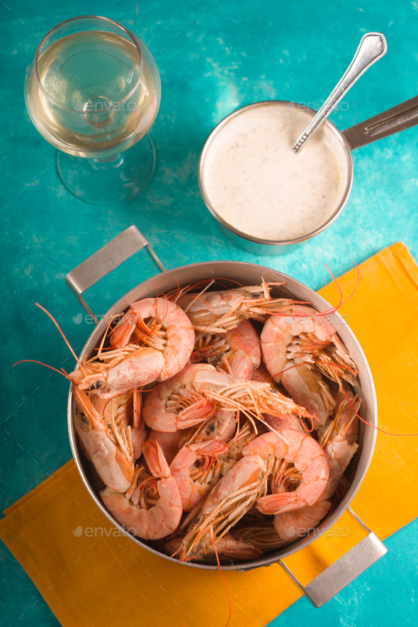 Shrimps on a yellow napkin, glass with white wine and sauce - Stock Photo - Images