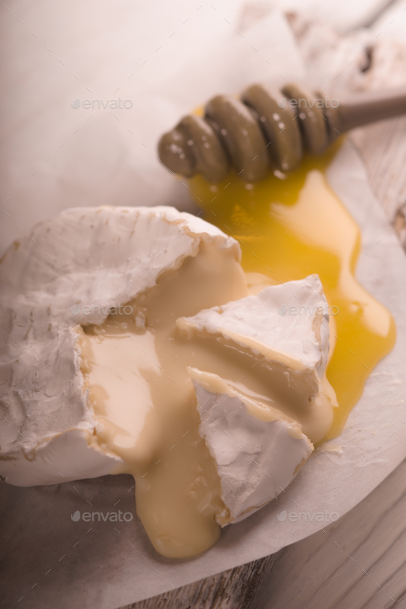 Brie cheese, slices, honey on parchment partial blur - Stock Photo - Images
