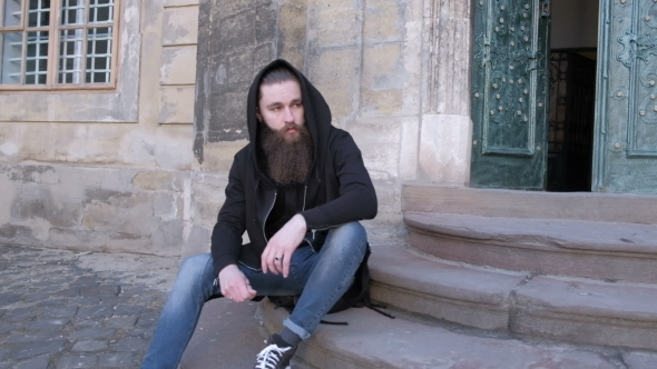 VideoHive Bearded Man Long Beard Brutal Hipster with Moustache on Serious Sits on the Steps 19784277