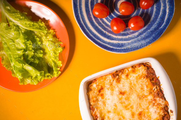 Lasagna, tomatoes, green salad on a yellow background - Stock Photo - Images