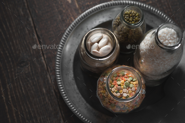 White beans, green beans, lentils and rice in cans on a dark background - Stock Photo - Images