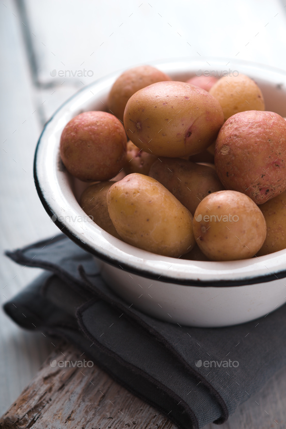 Raw potatoes in a white bowl on a napkin side view - Stock Photo - Images