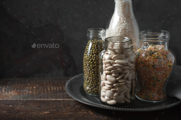 Lentils, white beans, rice in glass bottles copy space - Stock Photo - Images