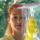Young Attractive Woman Washes a Window Using a Special Brush