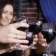 of Male and Female Hands Clinking Glasses with Red Wine To Each Other with Happy Faces in the