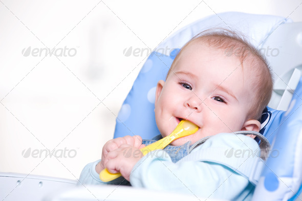 Happy baby with spoon - Stock Photo - Images