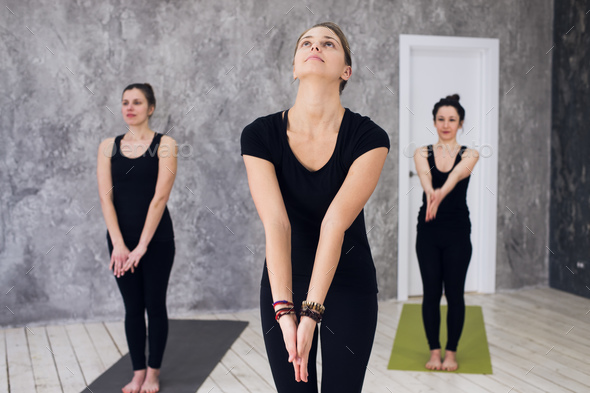 Young sportive trio group of girls are practicing yoga exercises in the studio - Stock Photo - Images