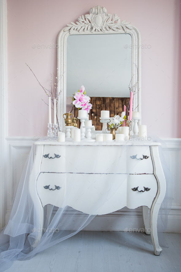 Shabby chic home design. Beautiful decoration table with a candles, flowers in front of a mirror - Stock Photo - Images