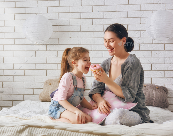 Mother and her daughter eating donuts - Stock Photo - Images