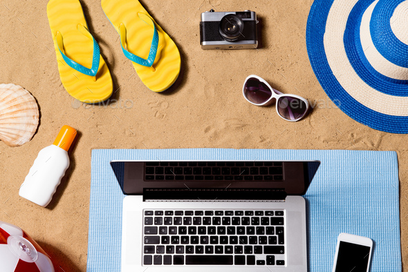 Summer vacation composition. Sandals, hat, laptop and smartphone - Stock Photo - Images