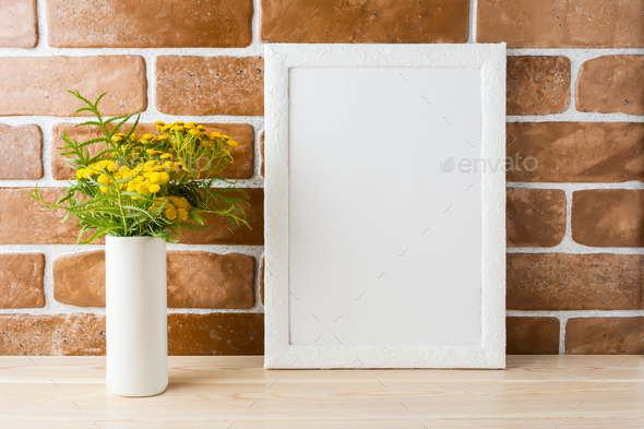 White frame mockup with yellow flowers near exposed brick walls - Stock Photo - Images