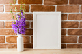 White frame mockup with campanula bouquet near exposed brick wal - PhotoDune Item for Sale
