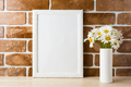 White frame mockup with daisy bouquet near exposed brick wall - PhotoDune Item for Sale