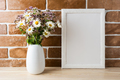 White frame mockup with wildflowers bouquet near exposed brick w - PhotoDune Item for Sale