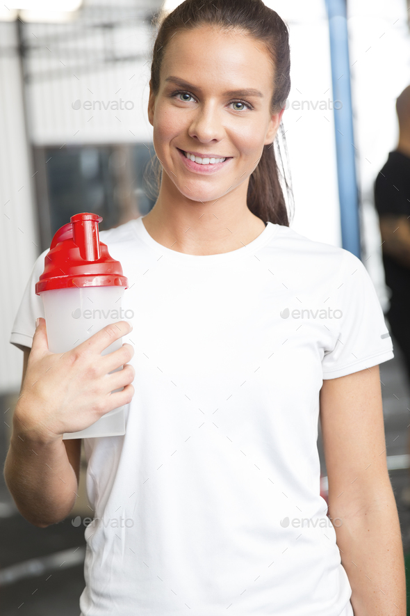 Smiling woman in workout outfit holding a drinking bottle at fitness gym - Stock Photo - Images