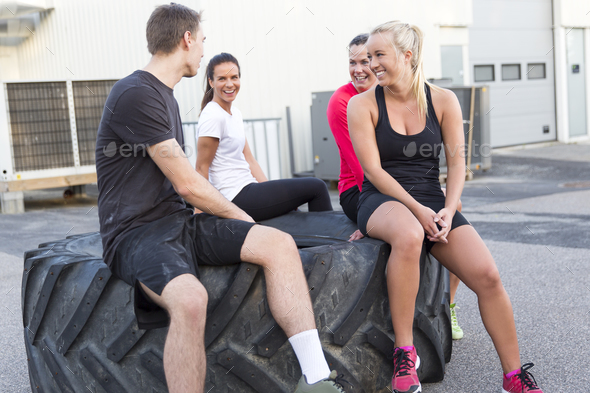 Happy workout team sitting on a tire and taking a break outdoor - Stock Photo - Images