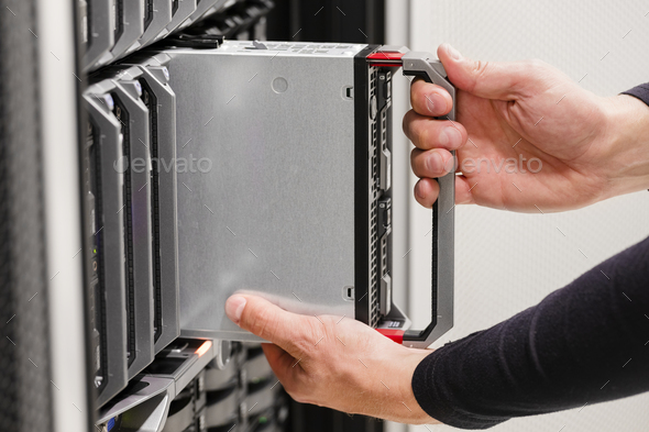 IT professional installs server cluster in large datacenter - Stock Photo - Images