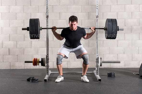 Man performing a crossfit back squat exercise - Stock Photo - Images