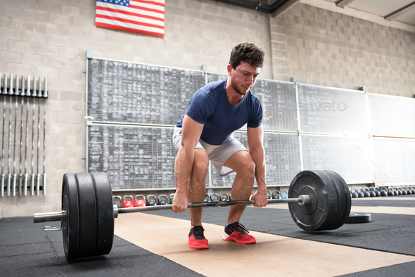 Athlete starting a deadlift in a crossfit gym - Stock Photo - Images
