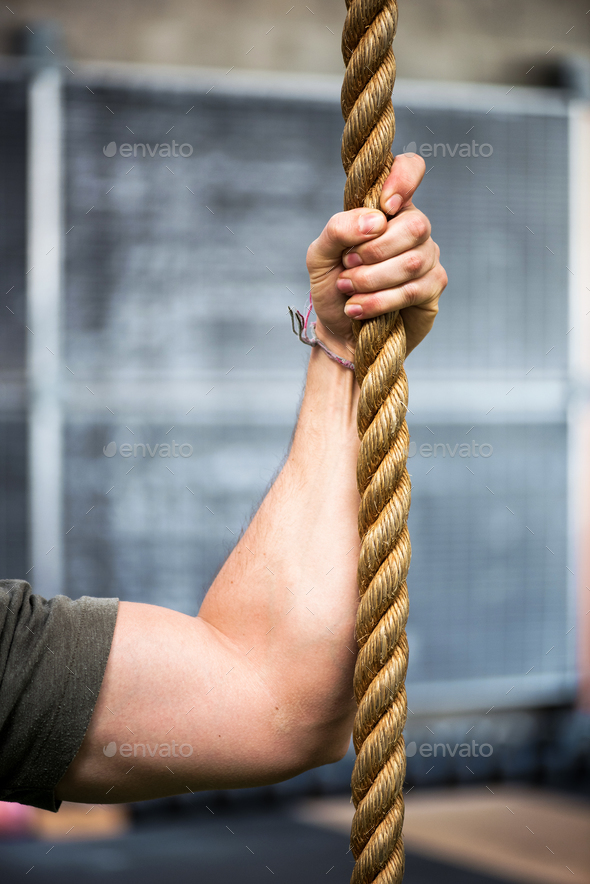 Strong muscular male arm holding a rope - Stock Photo - Images
