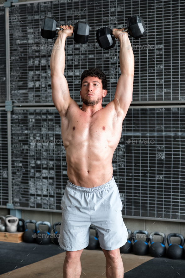 Bodybuilder exercising with dumbbells - Stock Photo - Images